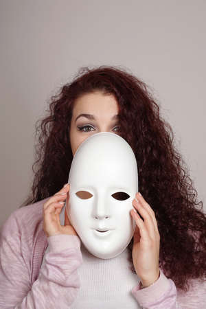 shy young woman taking off plain white mask Stockfoto