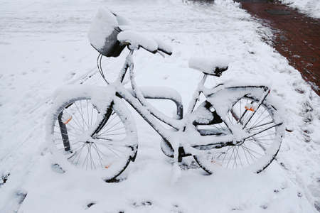 bike cover: abandoned bike or bicycle with snow cover in winter