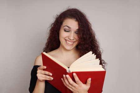 hardcover book: smiling teenage girl enjoys reading a funny hardcover book Stock Photo