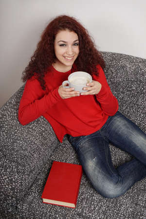 downtime: smiling teenage girl relaxing on couch at home drinking large cup of coffee Stock Photo