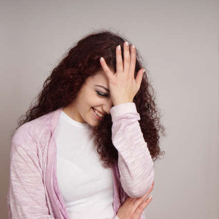 young woman feeling embarrassed with hand on forehead also known as facepalm Stockfoto