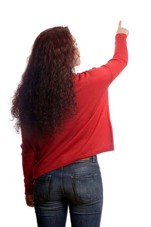 gift behind back: rear view of young woman pointing with finder at copy space