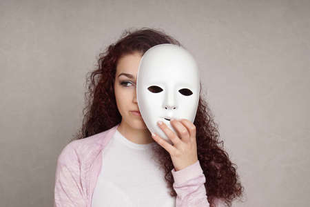 two faced: sad young woman hiding her face behind mask, identity or personality concept Stock Photo