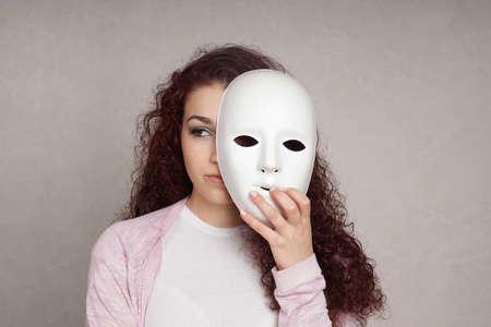 smutna młoda kobieta ukrywa twarz za maską, tożsamości i osobowości koncepcji Zdjęcie Seryjne