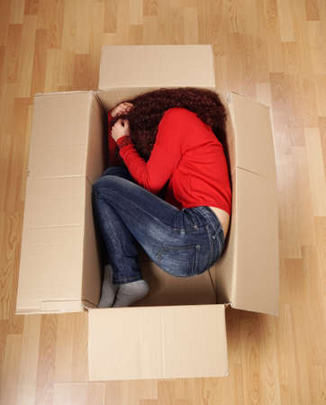 curled up: young woman lying curled up in cardboard box