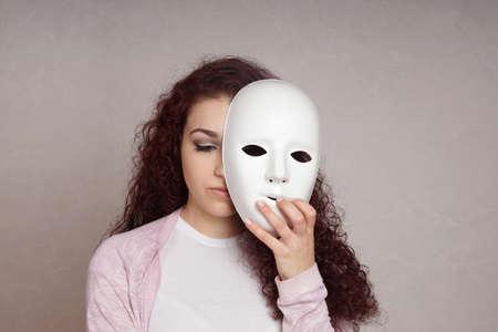 triste mujer joven deprimida que oculta su cara detrás de la máscara