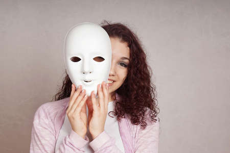two faced: smiling young woman peeking from behind mask