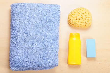 toalla: el cuidado del cuerpo tendido plano bodegón con una toalla, esponja, gel de baño y piedra pómez Foto de archivo