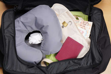 baggage: international travel concept, packing suitcase or bag with travel pillow, adapter, passport, money belt