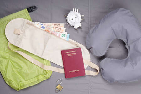 themed: themed flat lay with travel pillow, money belt, german passport, international travel adapter and padlock Stock Photo
