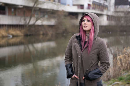 bleak: portrait of a young woman with pink hair standing by a river in bleak surroundings