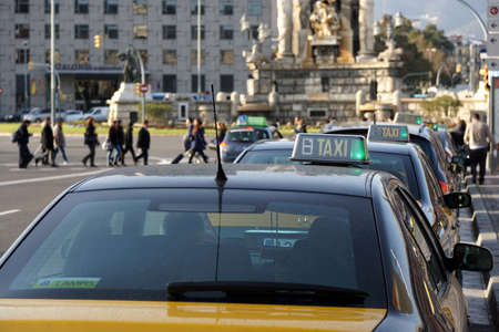 city traffic: Barcelona, Spain - Feb 29, 2016: Row of taxi cabs waiting for passengers at Placa dEspagna.