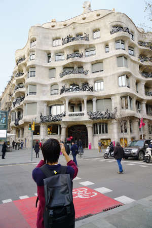 modernist: Barcelona, Spain - March 01, 2016: Tourist taking photograph of Casa Mila, also known as La Pedrera, by famous modernist architect Antoni Gaudi.