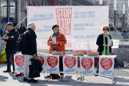 coincidir: Hannover, Alemania - 02 de abril de 2016: Detener a los activistas de TTIP repartiendo volantes a los transeúntes. Se planea una manifestación anti TTIP para el 23 de abril coincidiendo con la visita del presidente estadounidense Obama a Hannover. Editorial