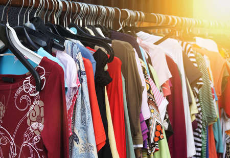 second hand: clothes rack with vintage second hand womens fashion. filtered image with sun flare. Stock Photo