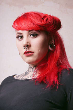 pierced ears: young alternative woman with facial piercings and tattoos Stock Photo