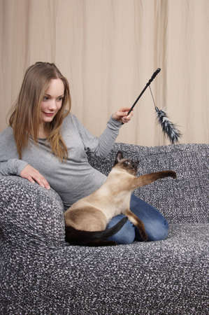young woman playing with air prey teaser cat toy Stockfoto