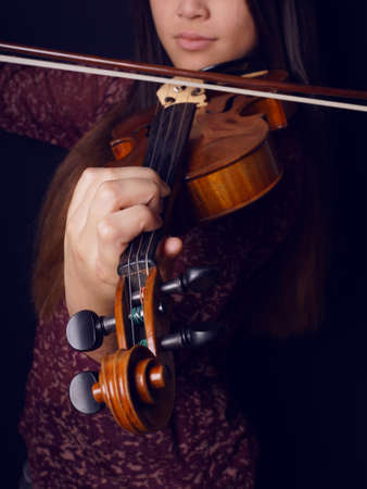 violin making: close-up of young asian woman playing violin with selective focus
