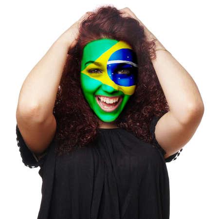 jubilate: girl with brazilian flag face paint. female soccer fan from brazil. Stock Photo