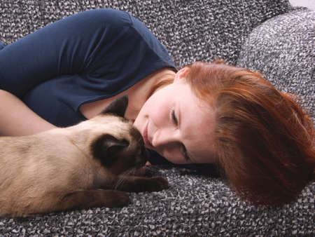 siamese cat: young woman relaxing with siamese cat at home on sofa