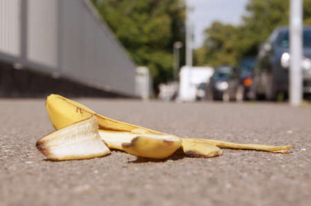 banana skin: discarded banana skin lying on pavement with selective focus