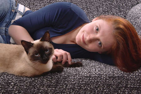 siamese cat: young woman relaxing with siamese cat at home on couch Stock Photo