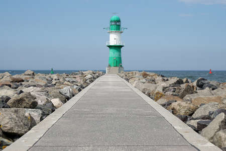 sea mark: footpath on pier leading to breakwater light or beacon at Rostock Warnemunde, Germany Stock Photo