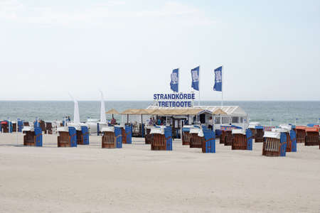 wicker bar: Rostock, Germany - May 30th, 2016: Beach bar with roofed wicker beach chair, known as Strandkorb in Germany, rental on a preseason day at Warnemunde strand.