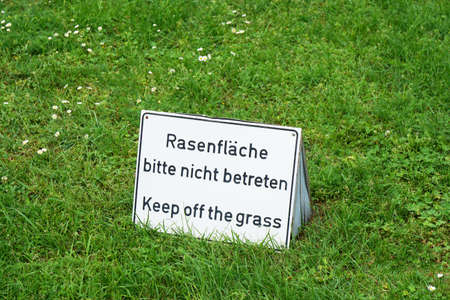 bilingual: bilingual keep of the grass sign in German and English Stock Photo