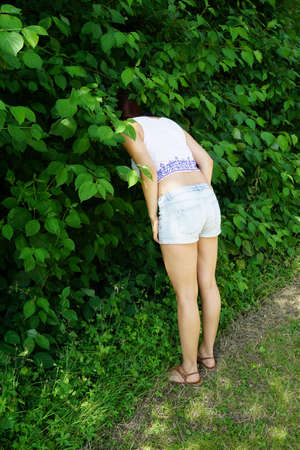 young woman sticking her head into bushes