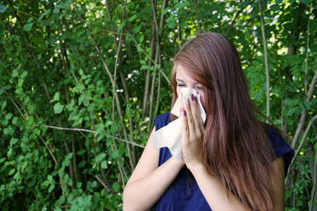 hayfever: young woman blowing her nose with paper tissue Stock Photo