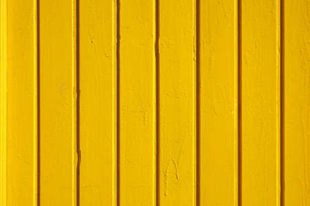 wall with wooden boarding painted yellow. background texture.