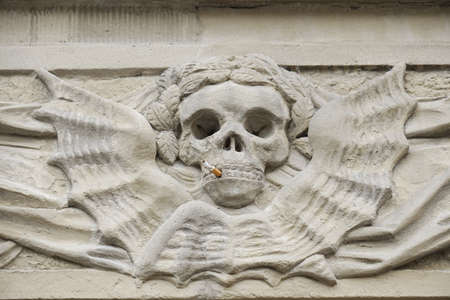 the kills: stone relief skull with cigarette. smoking kills concept.