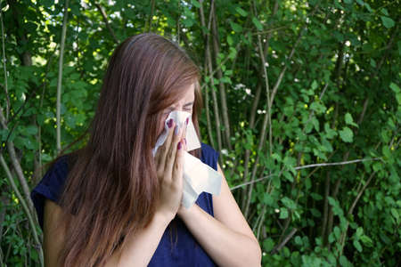 catarrh: young woman blowing her nose with paper tissue Stock Photo