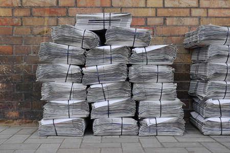 bundled: stacked and bundled tabloid newspapers on sidewalk