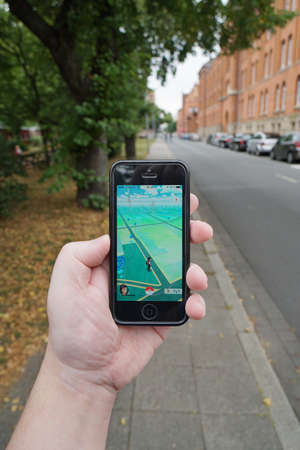 generation y: Hannover, Germany - July 23, 2016: Playing Pokemon Go on an iphone. The augmented reality game app was released in Germany on July 13. Editorial