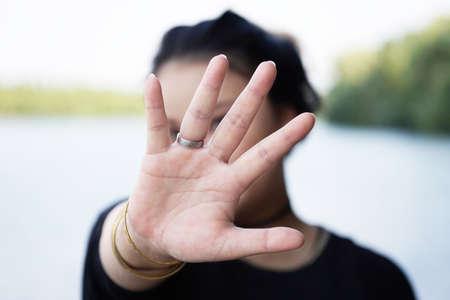 repel: woman hiding face behind hand. defense reaction.