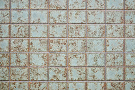 tiled wall: tiled exterior wall background with weathered green vintage tiling Stock Photo