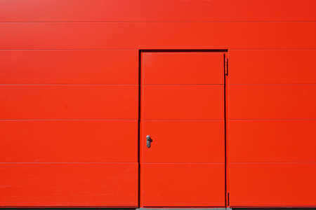 vibrant background: vibrant red exterior wall and door. background with copy space. Stock Photo