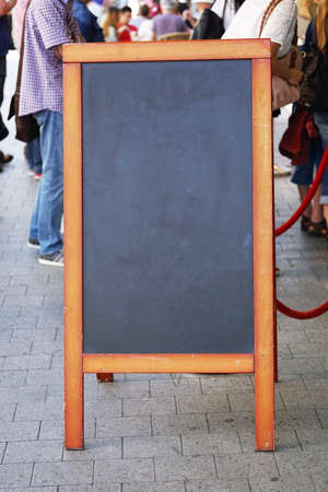pavement: blank blackboard pavement sign with unrecognizable people in the background. also known as customer stopper or sandwich board.
