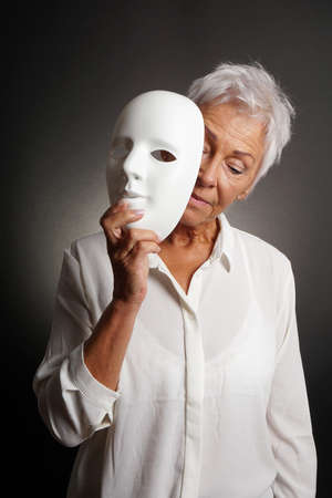 mature woman revaling sad face behind mask. depression concept.