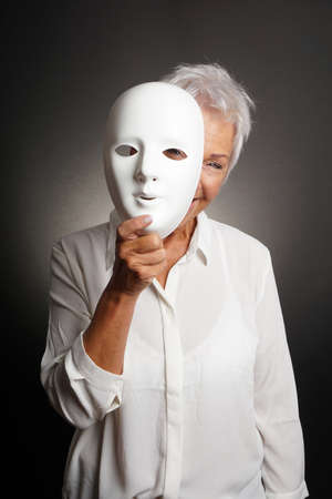 happy smiling playful mature woman peeking from behind mask Reklamní fotografie