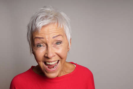 happy mature senior woman with short white hair laughing Standard-Bild