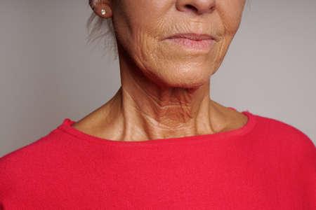 주름 피부 성숙한 여자의 목과 얼굴의 클로즈업 스톡 콘텐츠