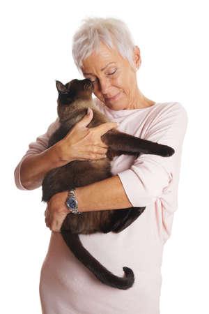 행복 한 성숙한 여자 siamese 고양이 그녀의 팔에 들고. 흰색으로 격리.