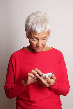 senior woman looking confused at her smartphone