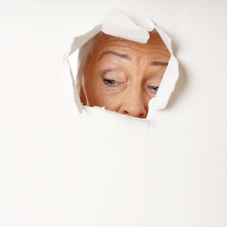 tearing down: curious mature woman looking through hole. with copy space.