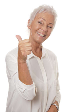 age 60: happy smiling mature woman in her sixties with trendy white short hair making thumbs up hand sign