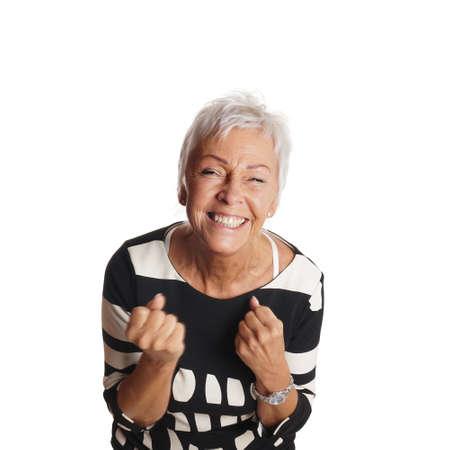 jubilating: overjoyed senior woman jubilating with clenched fists Stock Photo
