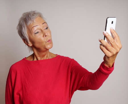 mature woman making a duck face while taking a selfie with her smartphone Standard-Bild